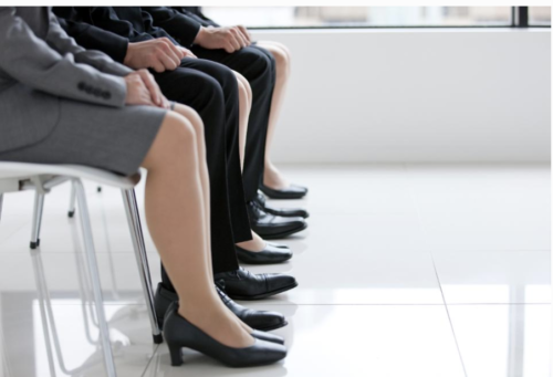 A side view of several job applicants in professional wear seated in a row, pictured from the waist down