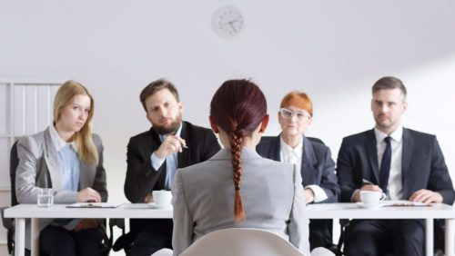 A stock image of a woman being interviewed by four executives